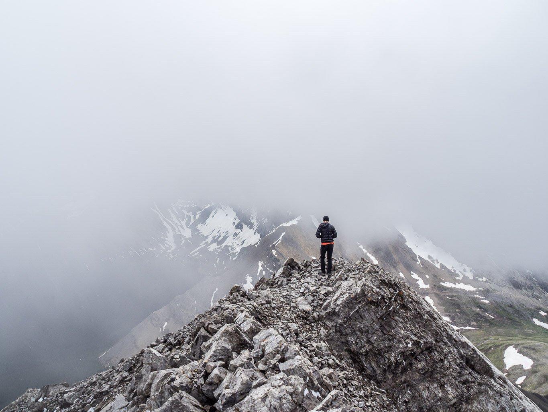 Phil stands just off the summit gazing towards a very hidden Golden Mountain across Fatigue Pass.