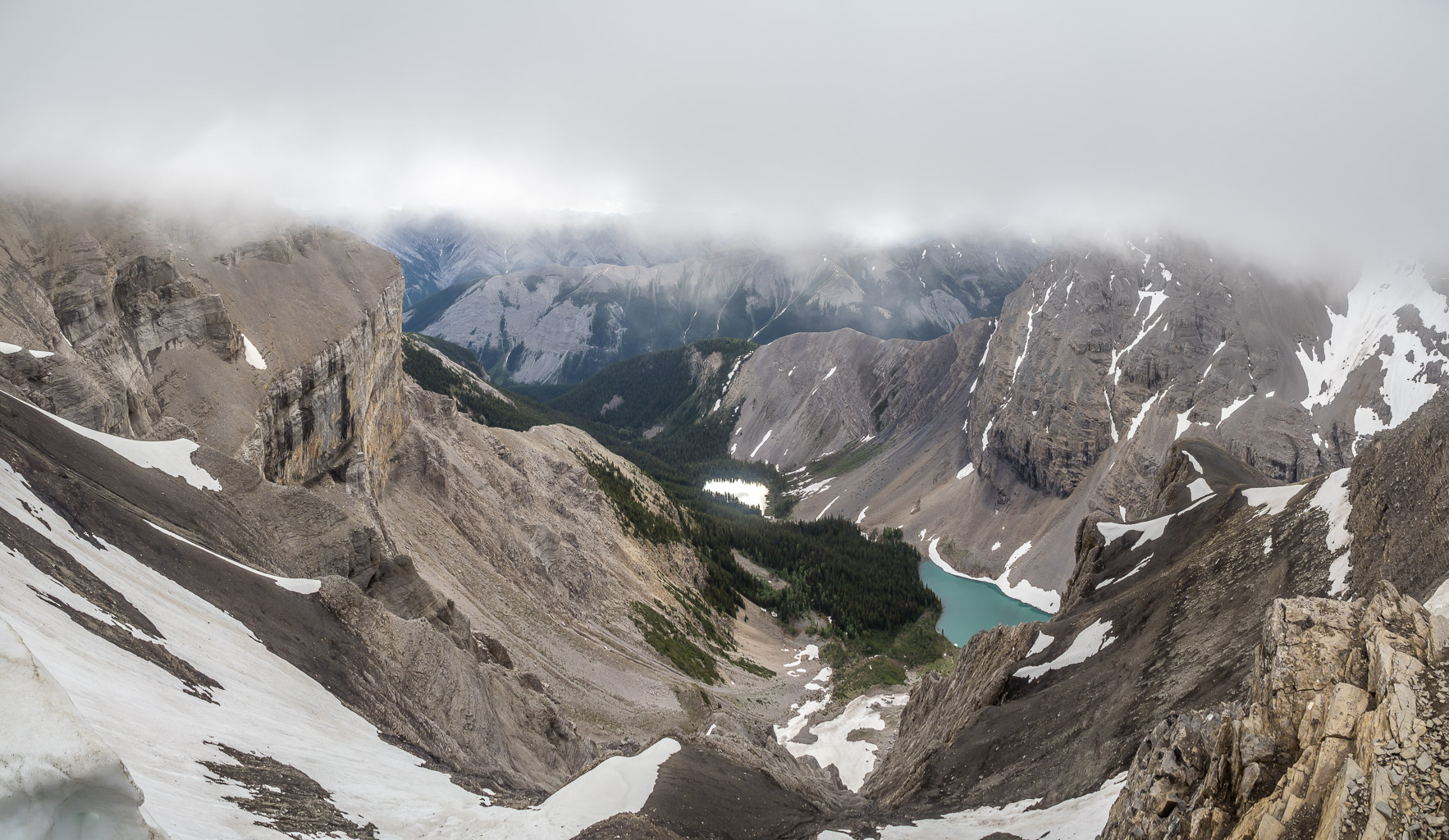 Entering the clouds, looking over the two lakes. The one at left is as bright as a mirror, reflecting the morning sun.